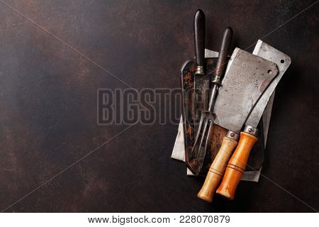 Vintage kitchen utensils, butcher, knife, fork over stone board. Top view with space for your text