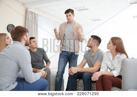 Young man talking about his problems during group therapy