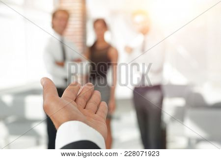 background image of businessman holding out hand for a handshake.