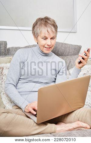 Senior with laptop computer surfing internet