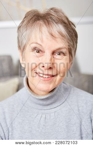 Kind and likeable senior woman or pensioner smiling content