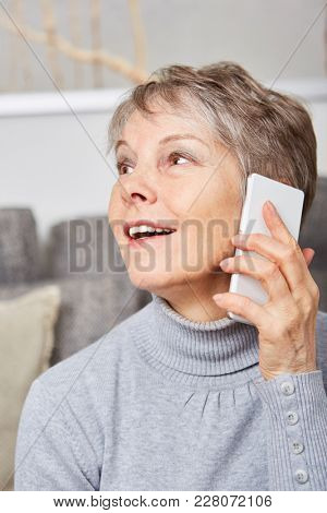 Senior woman with smartphone at home looks surprised