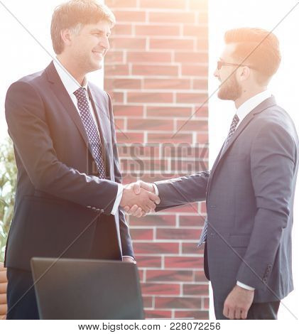 businessmen shaking hands while standing in office corridor