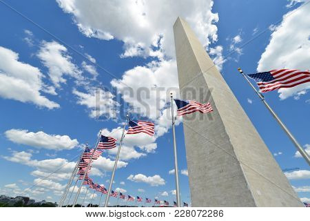 Washington Monument with waving United States National Flags on flagpoles - Washington DC United States