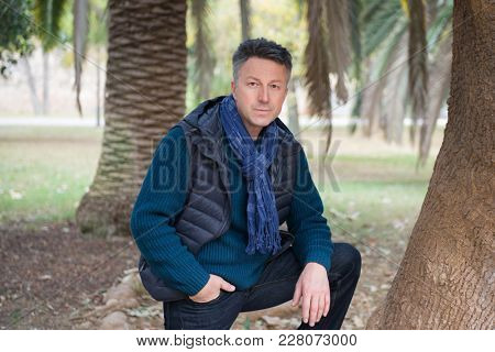 Handsome middle-aged man in Mediterranean park with palm trees. Attractive mid adult male model posing outddor.