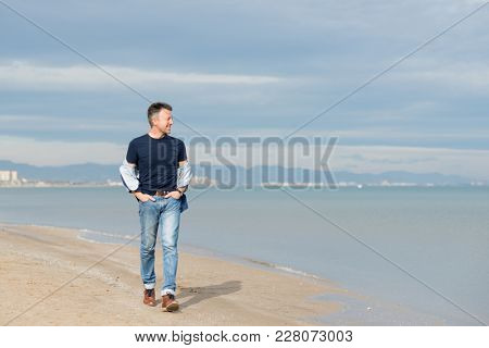 Handsome middle-aged man walking at the beach. Attractive happy smiling mid adult male model posing at seaside in blue jeans, t-shirt shirt. Full-length outdoor portrait of beautiful macho man.