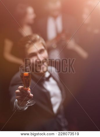 stylish young man raising his glass in a toast