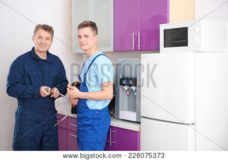 Plumber with young trainee in kitchen