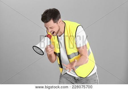 Worker with megaphone on grey background