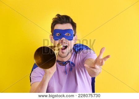 Young man in superhero costume with megaphone on color background
