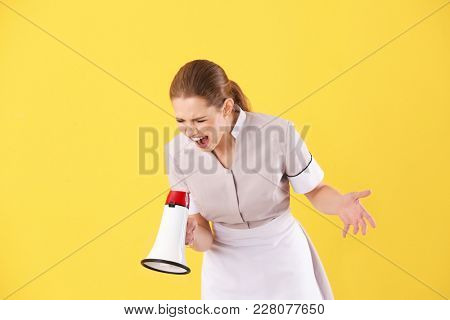 Young chambermaid shouting into megaphone on color background
