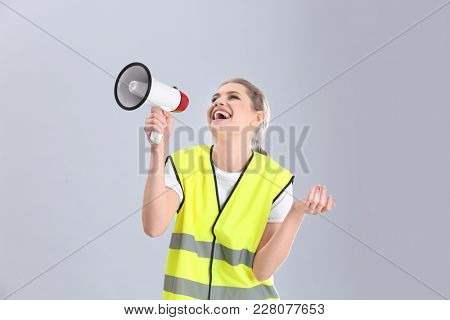 Young woman in reflective vest with megaphone on grey background