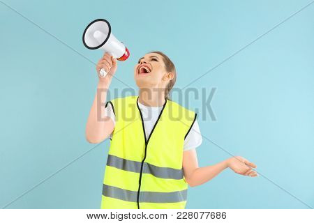 Young woman in reflective vest with megaphone on color background