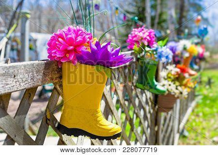 Silk flowers in a rubber boot garden.