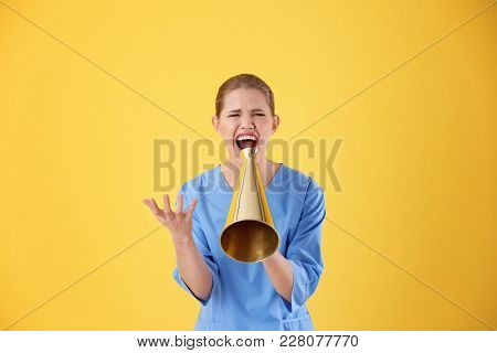 Young female doctor shouting into megaphone on color background