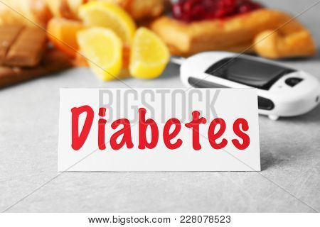 Card with word DIABETES and blurred digital glucometer on background