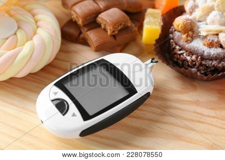 Digital glucometer and sweets on table. Diabetes diet