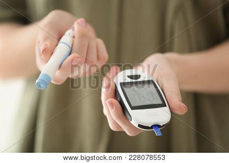 Diabetic woman holding digital glucometer and lancet pen, closeup