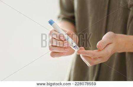 Diabetic woman taking blood sample with lancet pen, closeup