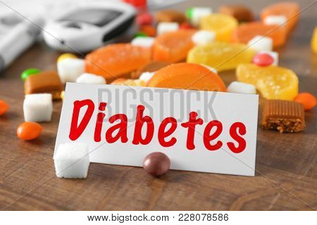 Card with word DIABETES and sweets on table
