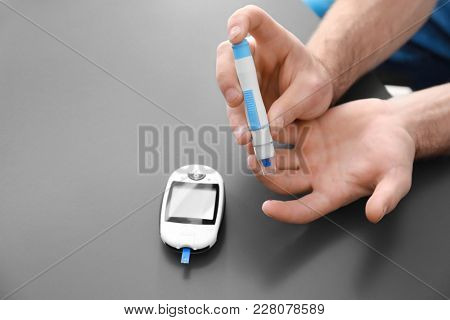 Diabetic man using lancet pen and digital glucometer on grey background