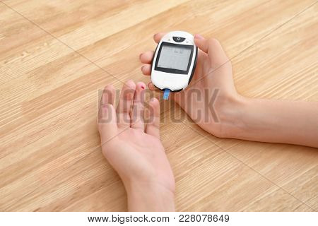 Diabetic woman using digital glucometer over table