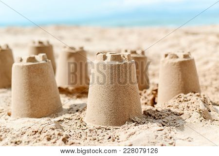closeup of several sandcastles on the sand of a beach, with the sea in the background