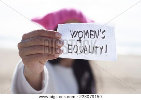 closeup of a young caucasian woman outdoors wearing a pink pussycat hat showing a piece of paper in front of her face with the text womens equality written in it