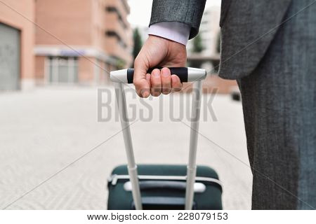 closeup of a young caucasian businessman in an elegant gray suit pulling a trolley by its handle on the street
