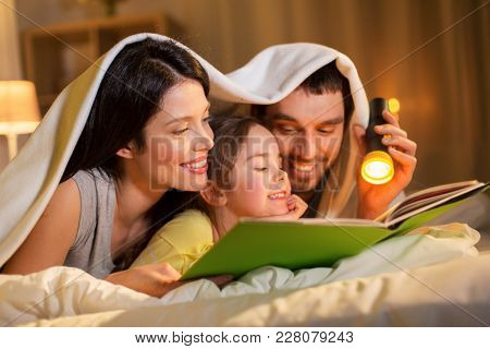 people and family concept - happy mother, father and little daughter reading book with torch light in bed lying under blanket at night at home