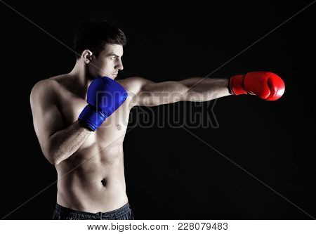 Man wearing red and blue boxing gloves on black background. Concept of political confrontation between American major parties - Democratic and Republican