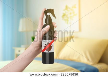 Woman holding bottle of anti bed bug detergent in bedroom