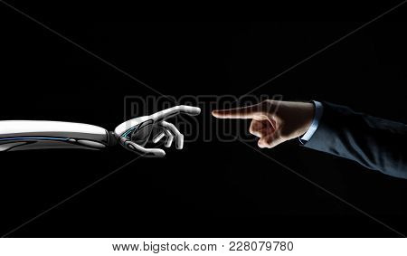 artificial intelligence, future technology and communication concept - robot and human hand connecting fingers on black background