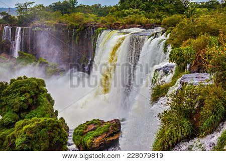 Travel to Argentina. The concept of exotic and active tourism. Powerful jets of the world famous waterfalls Iguazu. Picturesque basaltic ledges form the waterfalls