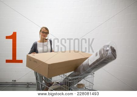 Pretty, young woman choosing the right furniture for her apartment in a modern home furnishings store - with a trolley, done shopping, leaving the store, going home with the goods
