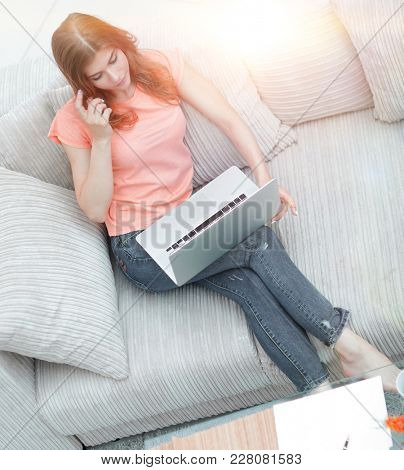 girl student with laptop sitting resting on the sofa.