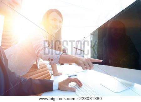 Satisfied girl is pointing at a blank monitor screen