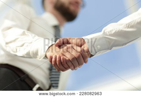 Close-up photo of handshake of two successful businessmen