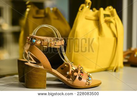 The Composition In The Window Of A Boutique: Women's Open Toe Shoes With A Heel With A Yellow Bag In