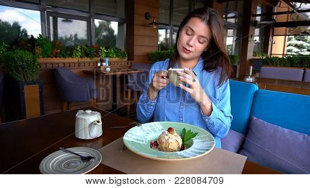 Beautiful European Girl Drinking Tea At Restaurant In . Female Person Sitting On Sofa With Teapot, C