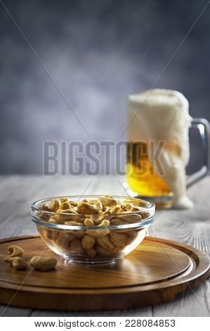 Glass Of Cold Beer On A Blue Background With Cashew Nuts.