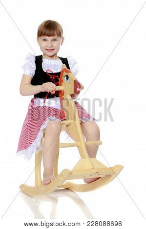 Little Girl Swinging On A Wooden Horse. The Concept Of A Happy Childhood, Games In Kindergarten And