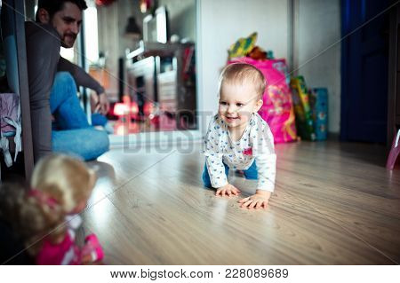 The Young Father Watches His Daughter, Who Plays On The Floor In The Room