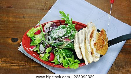 Juicy Seared Chicken Breast Slices Are Added To Green Tossed Salad,  Leaf Vegetables, Arugula, Lettu