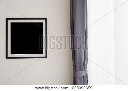Blank Picture Frame On Cement Wall With Modern Drape In Living Room.