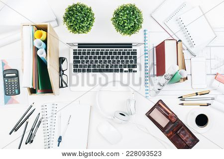 Top View Of White Office Desktop With Architectural Sketch, Supplies And Other Items. Blueprint And