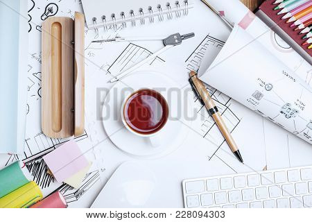 Close Up Of Office Workplace With Coffee Cup, Architectural Sketch And Other Items