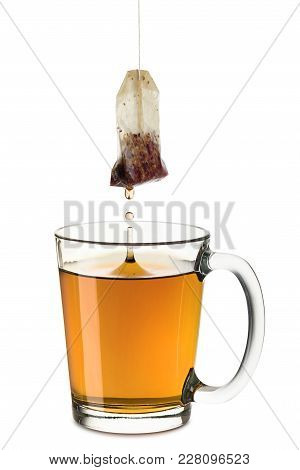 Glass Cup Full Of Tea With Tea-bag Dropping, On White Background