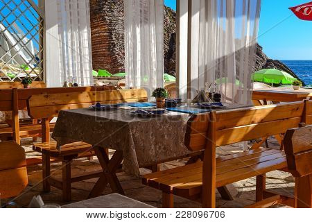 Table And Chairs Of The Restaurant Near The Sea. Sunny Day Is Summer. Without People. Montenegro