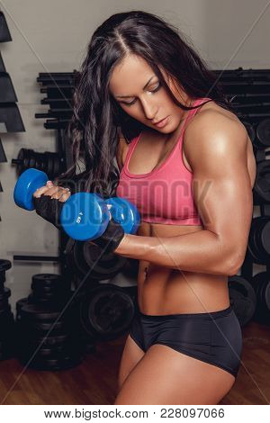 Athletic Fitness Woman Doing Biceps Exercise With Pair Of Dumbells.